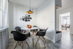 Round table and black chairs. White home interior with lamp, modern round table and black chairs stock photography