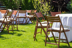 Round table covered with white cloth and chairs stand on a green lawn outdoors . Royalty Free Stock Images