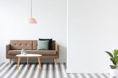Minimal living room interior. Round table in front of a brown sofa under pastel lamp in minimal living room interior Stock Photography