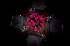 Round table modern serving. Round table with four plates and matching flower - dark mood Stock Photo