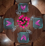 Round table modern serving. Round table with four plates and matching flower Royalty Free Stock Photos