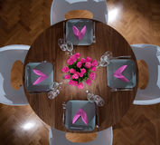 Round table modern serving. Round table with four plates and matching flower Stock Image