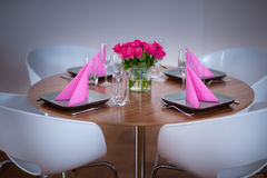 Round table modern serving. Round table with four plates and matching flower Royalty Free Stock Image