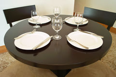 Round Table with Plates & Glass. Simple dining room with the round table and chairs Stock Photos