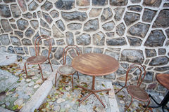 Round table and some chairs standing at stone wall of cafe Royalty Free Stock Photography