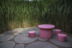 Round table and stools. Round and pink table with stools, surrounded by a reed hedge Royalty Free Stock Images