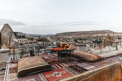 round table, traditional pillows and turkish carpet on terrace and beautiful view of traditional architecture and rocks stock images