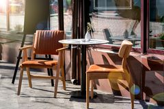 A round table with two chairs with backs on the wooden legs. A round table with two chairs with backs on the wooden legs of a summer cafe on the sidewalk near stock photography