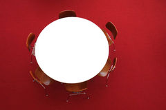 Round Table. A white round table, with six wooden chairs, on a red carpet Stock Photography