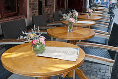 Round tables out of a restaurant. A ray of round tables with flowers on them out of a reataurant Stock Photography