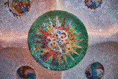 Round tile mosaic with sun on ceiling in the hall of hundred columns in the Barcelona Park Guell. False capstone. stock photos
