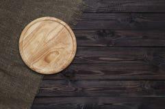 Round tnąca deska na ciemnym drewnianym stole zdjęcie royalty free