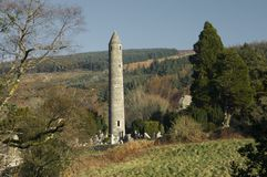 Round Tower and Graveyard in Glendalough. Round Tower in Glendalough, a glacial valley in County Wicklow, Ireland, renowned for an Early Medieval monastic stock photos