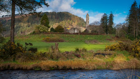 Round tower in Glendalough, Ireland. Charming landscape of Round tower in Glendalough with green meadow and dark river in front, Ireland Stock Photos