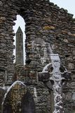 The Round Tower viewed through a window in a stone wall with a Celtic cross and grave stones in the foreground at the Glendalough. Monastic Site in Wicklow royalty free stock photos