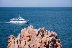 Round-trip boat sailing along the coast Royalty Free Stock Image