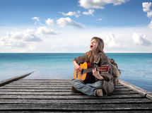 Round tripping. Young woman in alternative clothes singing and playing music on a wharf Royalty Free Stock Images