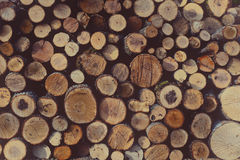 Round unbroken firewood stacked in a woodpile, rustic vintage to. Round unbroken firewood stacked in a woodpile. Rustic background in vintage tones stock photo