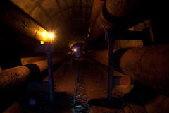 Round underground tunnel of heating duct with rusty tube and cable Stock Photos