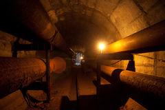 Round underground tunnel of heating duct with rusty tube and cable Royalty Free Stock Images