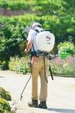 Round Up. A man spraying Round Up weed killer in a botanical garden royalty free stock image