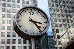 Round urban clock on a pole in Canary Wharf, London Stock Image