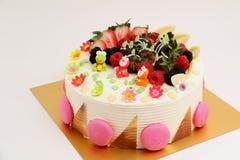 Round vanilla cake decorated with fresh fruits Stock Image