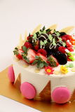 Round vanilla cake decorated with fresh fruits Stock Images