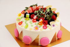Round vanilla cake decorated with fresh fruits Stock Photos