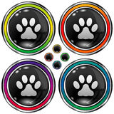 Round vector button with paw print icon. Shiny round vector button set with paw print icon on black background Royalty Free Stock Images