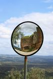Round view mirror in Evoramonte. Curved corner traffic mirror on the roadside of Evoramonte, Portugal showing medieval fortification wall in the reflection with Stock Images