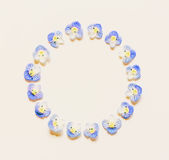 Round vintage frame made of small blue flowers on a white background with space for text Stock Photography