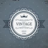 Round vintage label with ribbon, royal crown and grunge background. Royalty Free Stock Photography