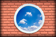 Round and vintage window against blue sky on a brick wall buildi Stock Photography