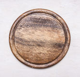Round, vintage wooden cutting board with text area wooden rustic background top view close up Royalty Free Stock Photos