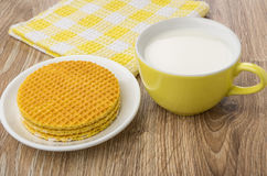 Round wafer with stuffed in saucer, milk in cup Royalty Free Stock Images