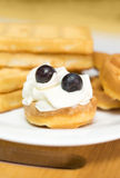 Round waffle with cream and blueberries on a white plate. Stock Image