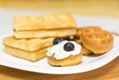 Round waffle with cream and blueberries on a white plate on a ta Royalty Free Stock Photos