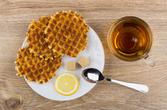 Round waffles, lemon, sugar, teaspoon in plate and tea Royalty Free Stock Photo