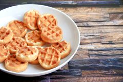 Round waffles in a white plate on a brown wooden background stock photos