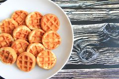 Round waffles in a white plate on a brown wooden background stock photography