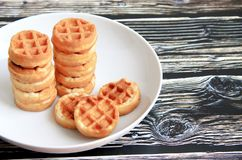 Round waffles in a white plate on a brown wooden background royalty free stock image