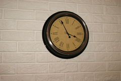 Round wall clock in light brick texture stock photos
