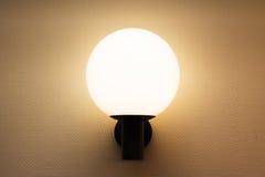 Round wall lamp illuminated white wall Royalty Free Stock Images