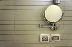Round cosmetic mirror on wall with Electric white socket in the bathroom. Round washroom adjustable mirror on wall royalty free stock photography