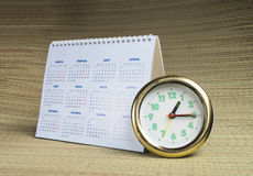Round watch with calendar. Round watch with desk paper calendar on beige background Royalty Free Stock Photo