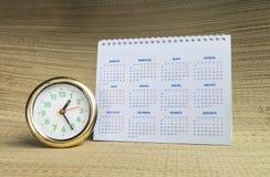 Round watch with calendar. Round watch with desk paper calendar on beige background Stock Image