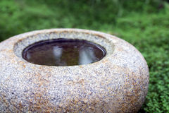 Round water basin or bird bath of natural stone granite Royalty Free Stock Images