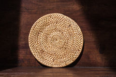 Round weave rattan tray, countryside household, on retro wooden background with shade and shadow, shadow environment at Stock Photography