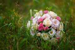 Round wedding bouquet lay in the grass. Royalty Free Stock Photos